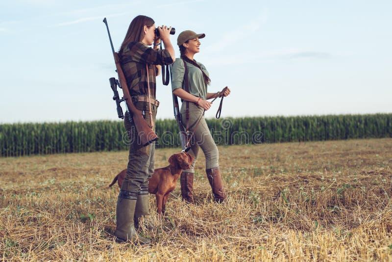 Cazadores de las mujeres con el perro de caza fotografía de archivo