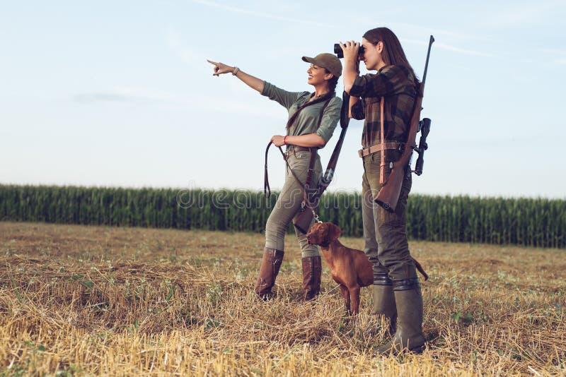 Cazadores de las mujeres con el perro de caza imagenes de archivo