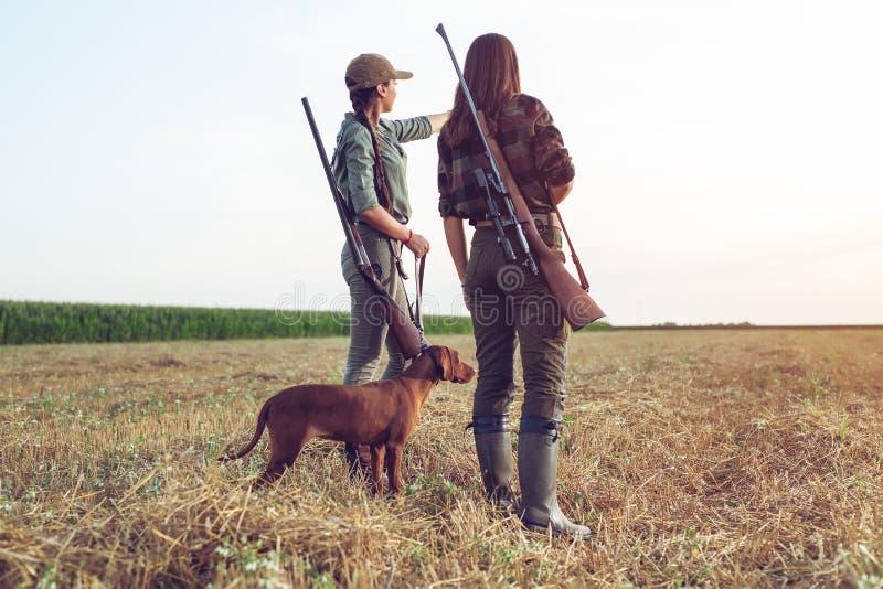 Cazadores de las mujeres con el perro de caza imagen de archivo