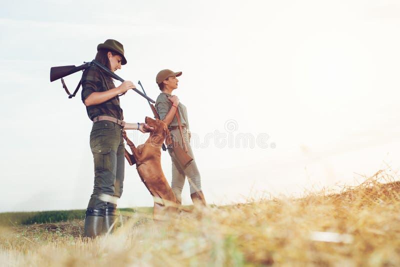 Cazadores de las mujeres con el perro de caza fotografía de archivo libre de regalías