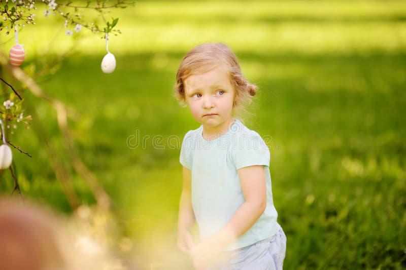 Cazas lindas de la niña para el huevo de Pascua en árbol de florecimiento de la rama imagen de archivo libre de regalías