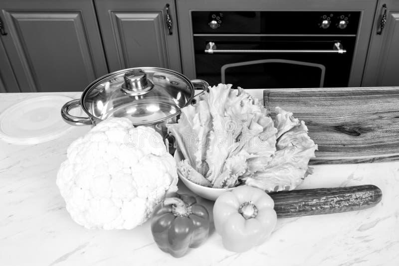 Cazo y coliflor, pimientas, pepino, hojas de la ensalada en la tabla de cocina foto de archivo