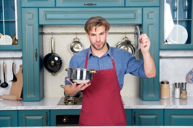 Cazo y tapa del control del hombre del cocinero en cocina fotos de archivo
