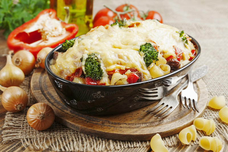 Cazuela con la carne, las pastas, el bróculi y los tomates imagen de archivo