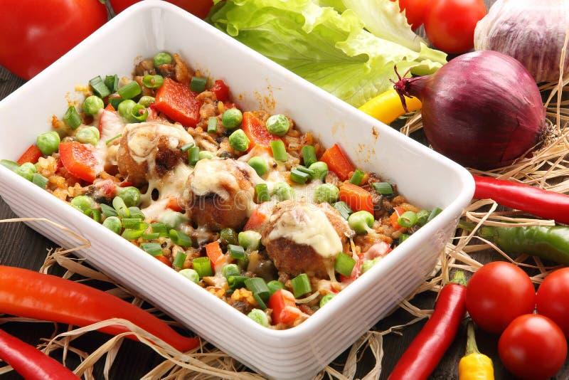 Cazuela con las albóndigas y las verduras del arroz en backgroun de madera fotografía de archivo