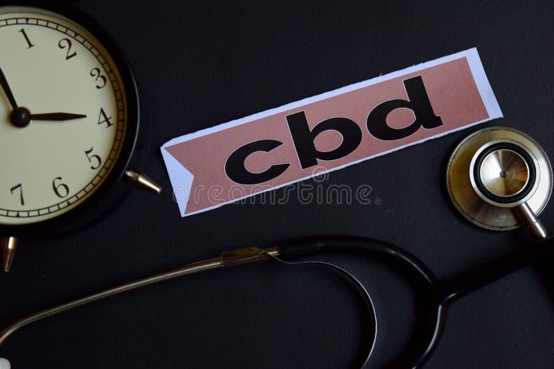 CBD auf dem Druckpapier mit Gesundheitswesen-Konzept-Inspiration Wecker, schwarzes Stethoskop lizenzfreies stockbild