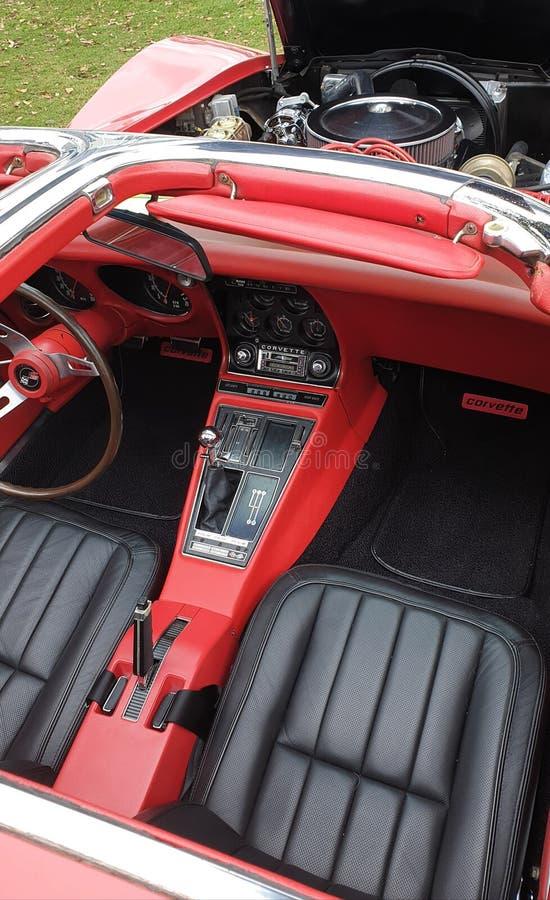 Cca Chevrolet Corvette som 1960 är rött piskar inre med svarta platser arkivfoton