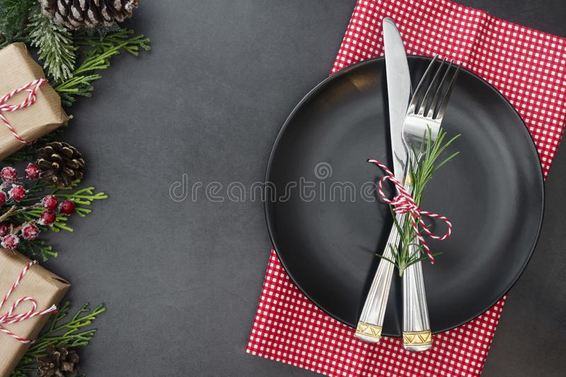 cChristmas place setting with ribbon. Black plate with fork and knife, decorated. Top view, copy space stock image