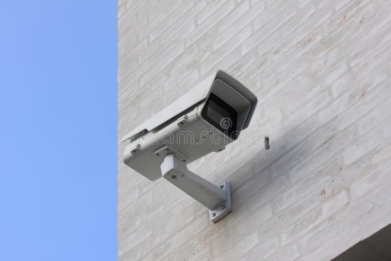 CCTV在与天空蔚蓝的白色大厦登上的监视器在背景 免版税库存照片