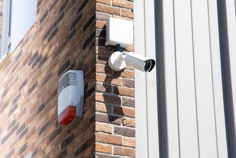 CCTV在大厦的安全监控相机在城市有在技术概念的砖墙背景 库存照片