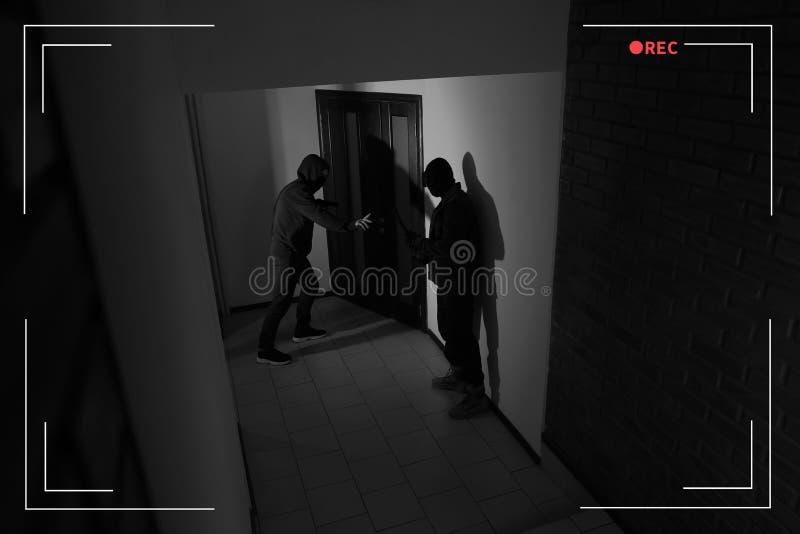 CCTV摄像头里,有枪和乌鸦的危险罪犯闯入公寓 库存图片