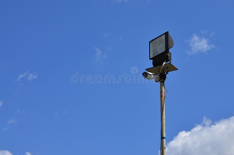CCTV照相机和一盏方形的聚光灯在反对蓝天的一根金属杆登上 组织的录影监视syste 免版税库存图片