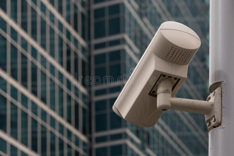 CCTV camera against view of modern buildings through office window royalty free stock photos
