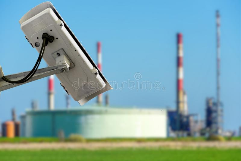 CCTV camera concept with fuzzy oil storage tanks on background. CCTV camera concept with fuzzy oil storage tanks on blurry background stock photography