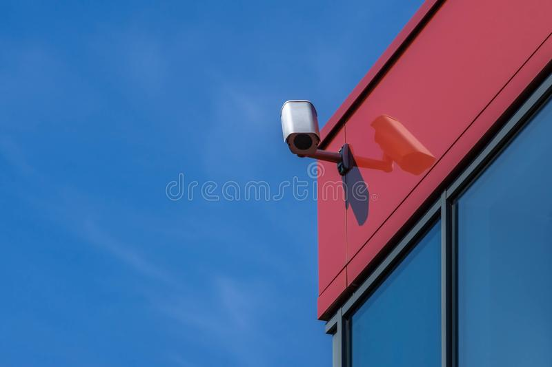 CCTV camera on modern building. Security camera on red wall, blue sky background. Copy space. CCTV surveillance camera installed on modern red building wall stock photography