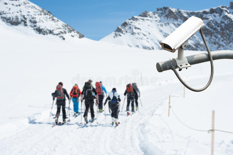 CCTV Camera Operating on snow mountain with people hiking in background royalty free stock photography