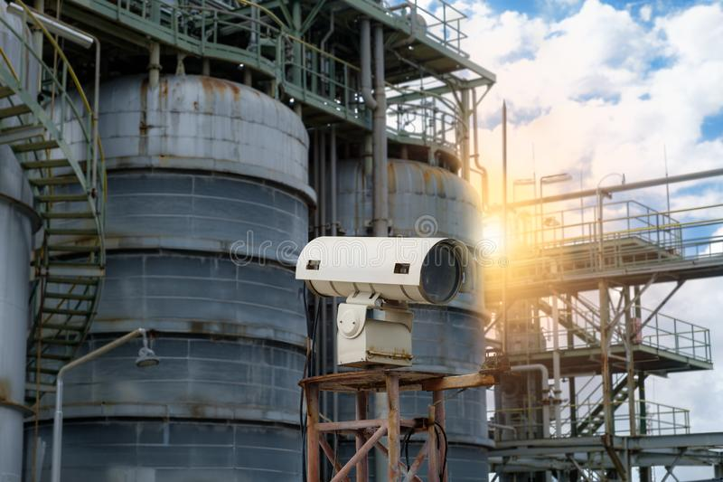 CCTV Camera for security in factory and storage tank at sunset time 石化厂侧影安全摄像机 免版税图库摄影