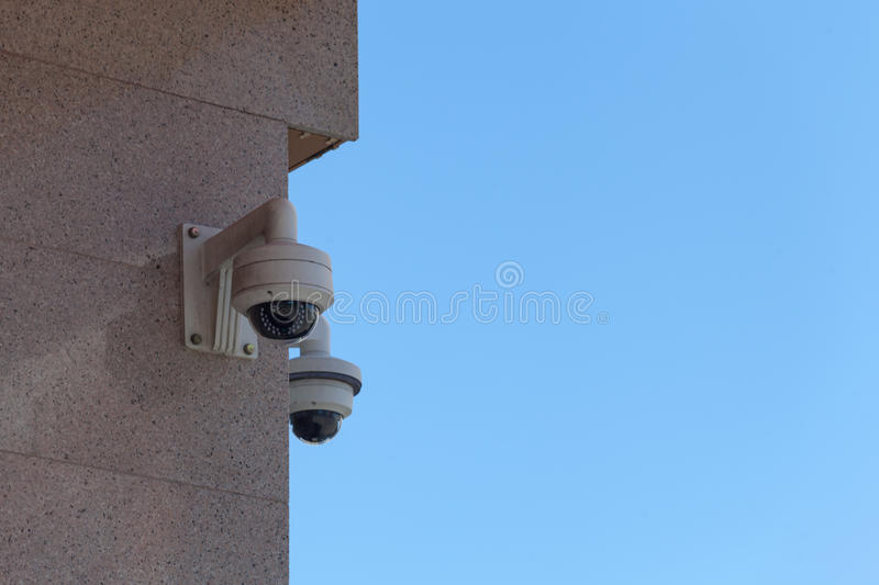 Cctv camera security on the wall in city. Cctv camera security on the wallAgainst the background of blue sky royalty free stock images