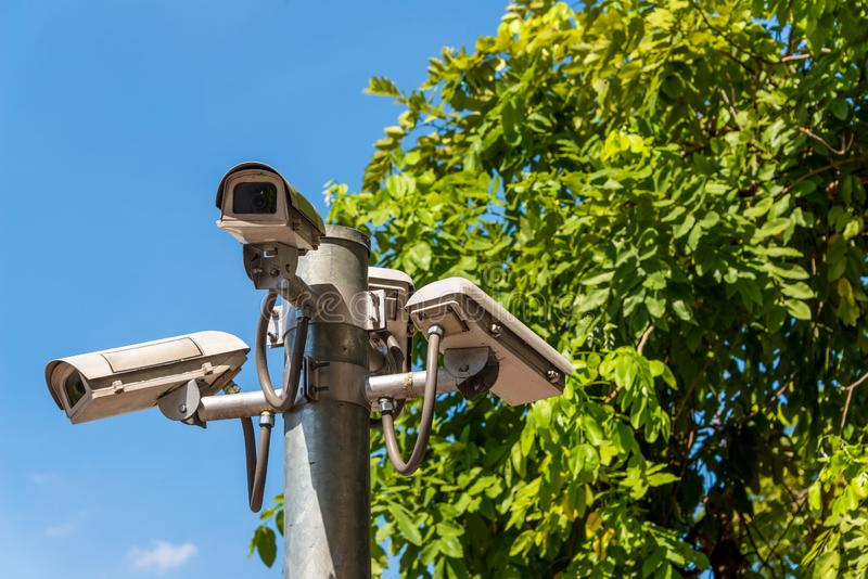 CCTV camera on street for concept of surveillance monitor. Multi angle CCTV camera system operating watching city security in green park background. Concept of royalty free stock image