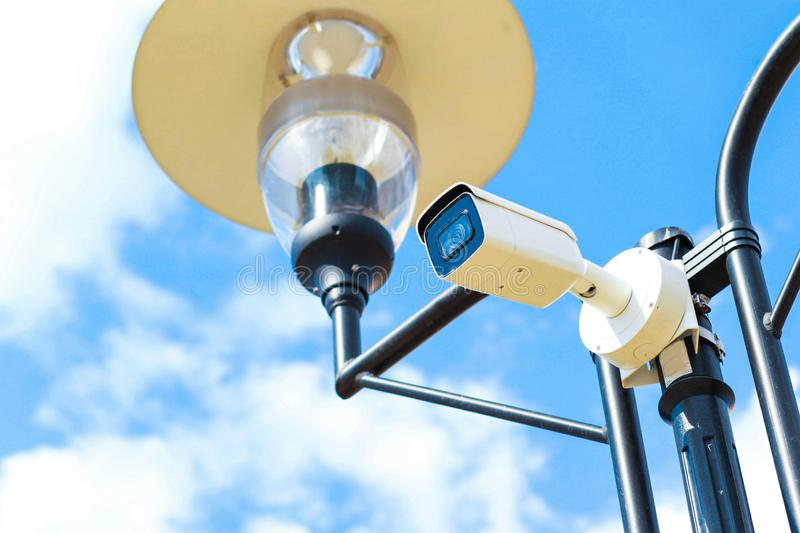 CCTV camera on the street and park. Face recognition system in the crowd stock photo
