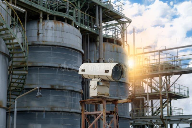 CCTV-kamera för säkerhet i fabrik och lagringstank vid solnedgång Säkerhetskamera för silhuetter i petrokemiska anläggningar royaltyfri fotografi