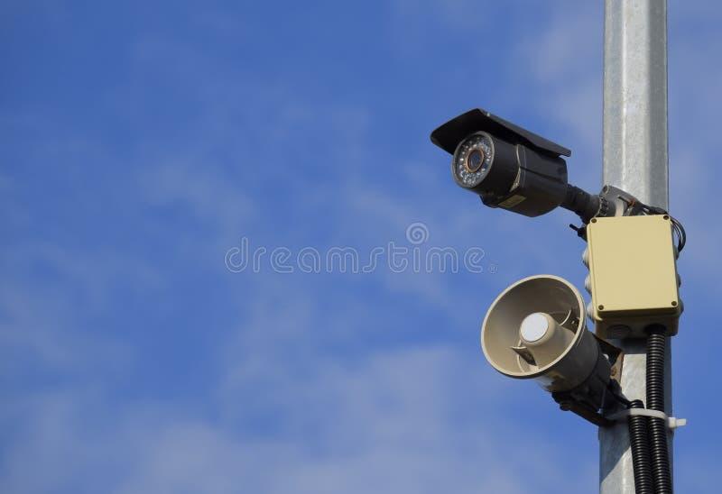 Cctv-kamera och högtalarelarm på en pol mot en blå himmel arkivfoto