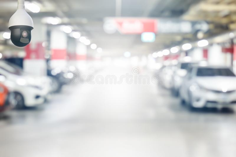 Cctv security camera on blur underground cars parking garage with light on exit way use as background stock image