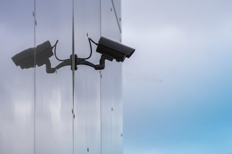 CCTV security camera on modern glass building wall with reflection royalty free stock photo