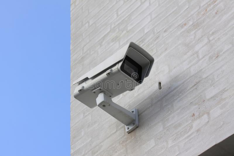 CCTV surveillance camera mounted on white building with blue sky in background royalty free stock photos