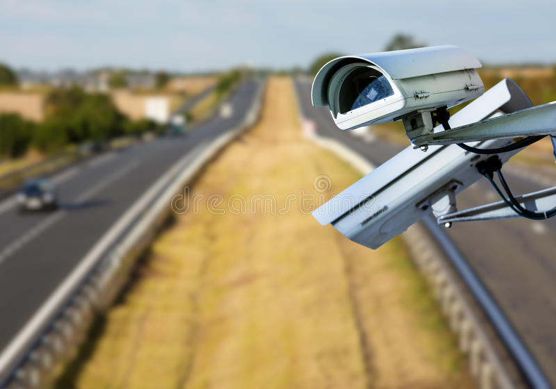 CCTV system on the road. Security CCTV camera or surveillance system with road highway on blurry background royalty free stock photo