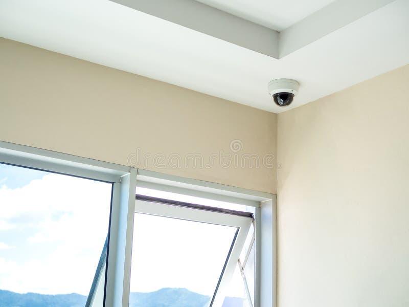 Cctv-systemsäkerhet Rund CCTV-kamera på tak i hörnet av gångbanan i andelslägenhet royaltyfri fotografi