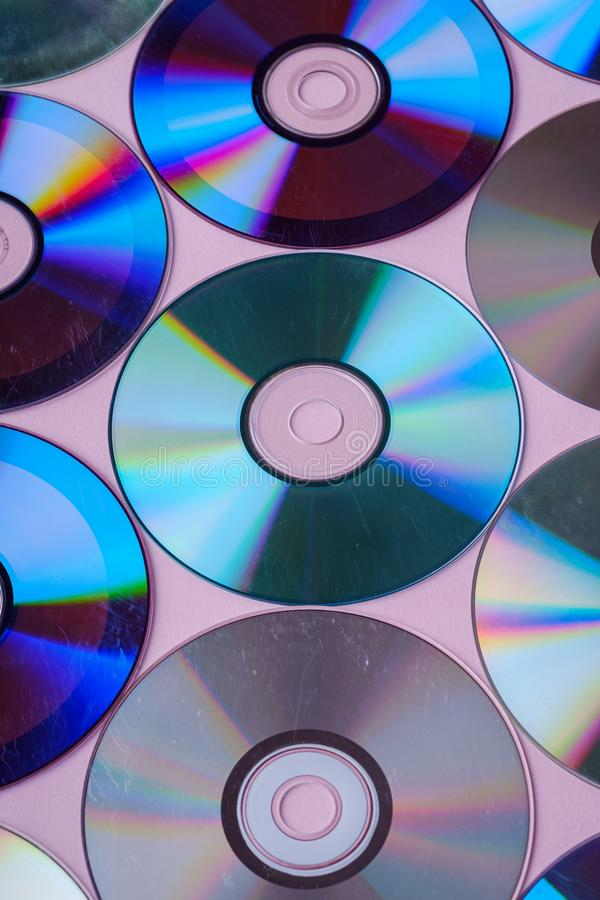 CD的DVD光盘盘分散作用折射光的反射在桃红色背景的颜色纹理 免版税库存图片
