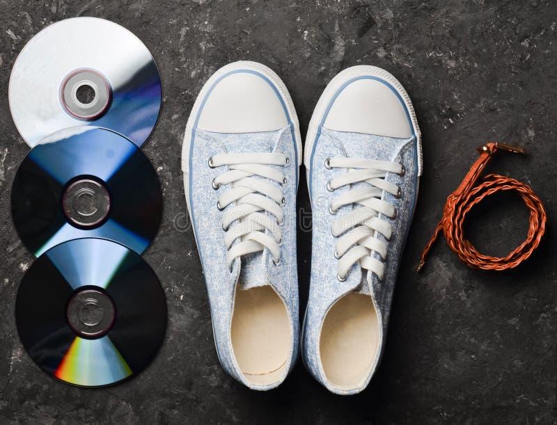 CD,皮带,从80s的时髦的减速火箭的运动鞋在黑色 库存图片