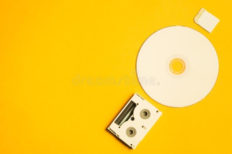 CD και κάρτα μνήμης στο κίτρινο υπόβαθρο Ψηφιακή τηλεοπτική κασέτα διάστημα αντιγράφων στοκ εικόνα με δικαίωμα ελεύθερης χρήσης