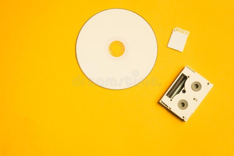 CD και κάρτα μνήμης στο κίτρινο υπόβαθρο Ψηφιακή τηλεοπτική κασέτα διάστημα αντιγράφων στοκ εικόνες