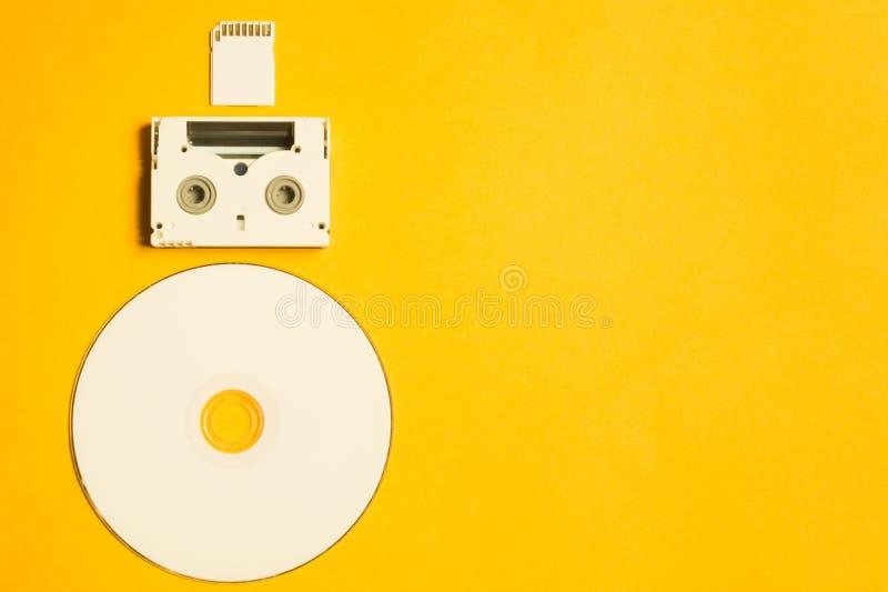 CD και κάρτα μνήμης στο κίτρινο υπόβαθρο Ψηφιακή τηλεοπτική κασέτα διάστημα αντιγράφων στοκ φωτογραφίες