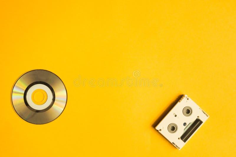 CD και ψηφιακή τηλεοπτική κασέτα στο κίτρινο υπόβαθρο διάστημα αντιγράφων στοκ φωτογραφίες