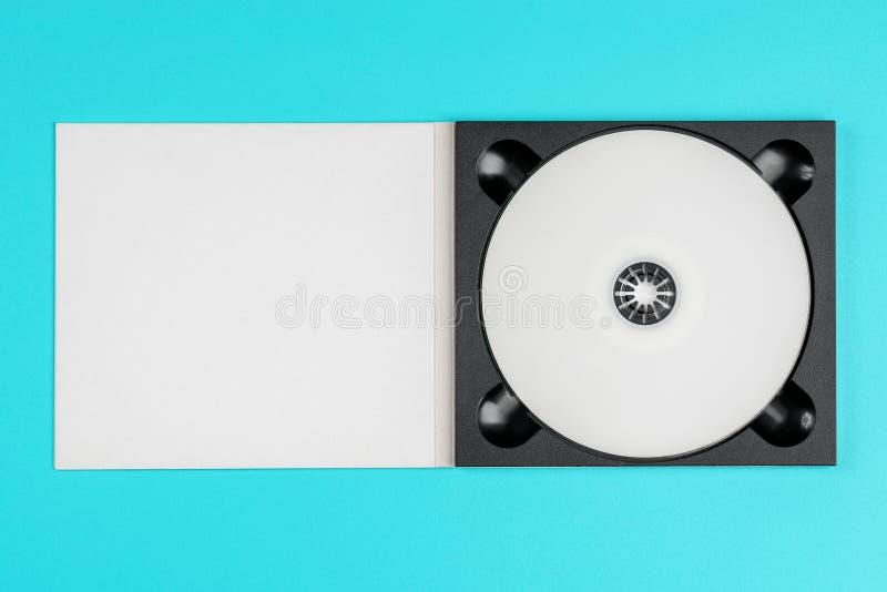 Cd blanco en caja negra en fondo verde en colores pastel fotos de archivo libres de regalías