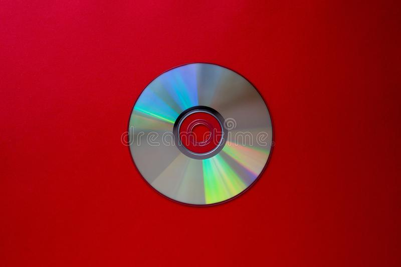Cd compact disc on a Dark red background top view with copy space. Close-up stock photo
