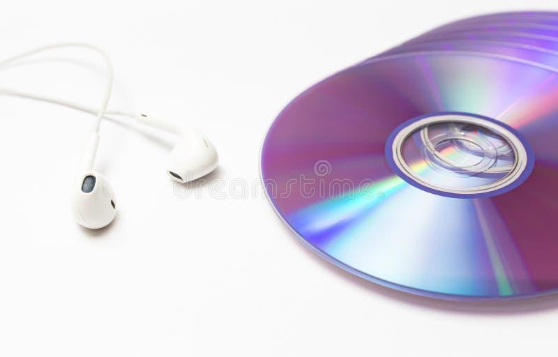 Cd, discos del DVD con los auriculares imágenes de archivo libres de regalías