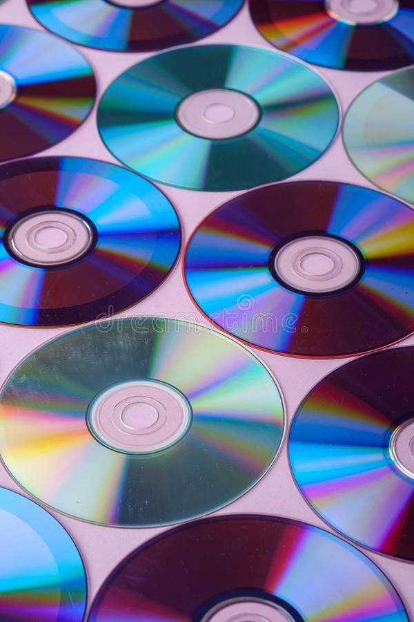 CD DVD compact disc disk dispersion refraction reflection of light colors texture on pink background. Close up stock image