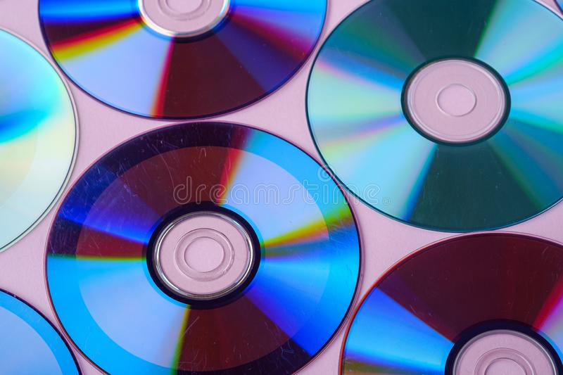 CD DVD compact disc disk dispersion refraction reflection of light colors texture on pink background. Close up stock photo