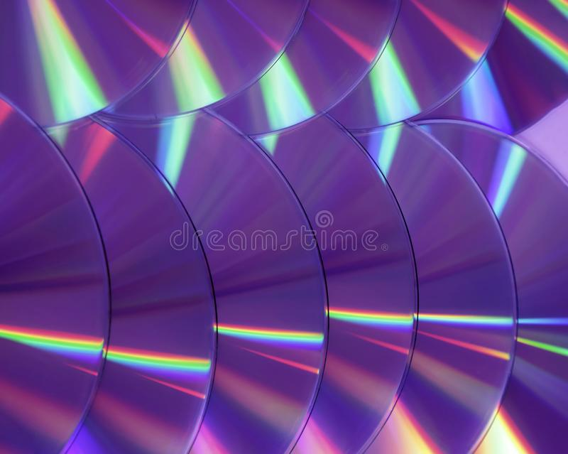 CD DVD disc colorful compact background rainbow shine color pantone ultra violet pink purple deep proton. Close up group of violet and purple DVD discs stock image