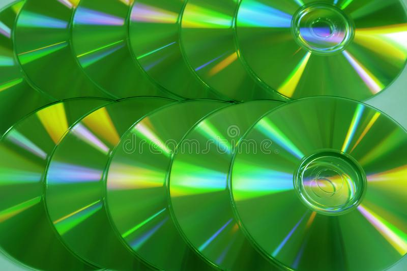CD DVD disc colorful compact background rainbow shine pantone ultra green UFO yellow. Close up group of green and yellow DVD discs. Background from colorful stock photo