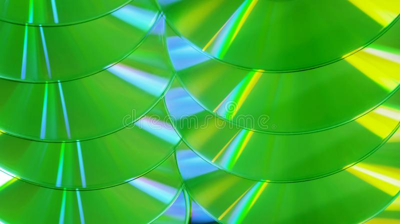 CD DVD disc colorful compact background rainbow shine pantone ultra green UFO yellow. Close up group of green and yellow DVD discs. Background from colorful royalty free stock photography