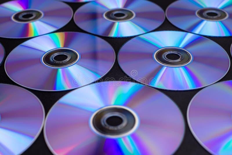 CD/DVDs som ligger på en svart bakgrund med reflexioner av ljus royaltyfri foto