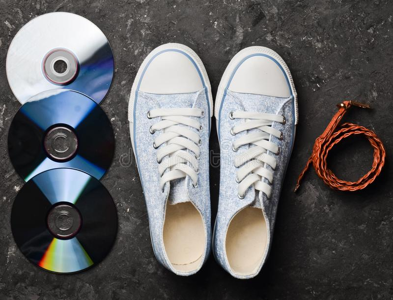 CD, leather strap, stylish retro sneakers from 80s on a black. Concrete floor. Fashion accessories and digital attributes. Top view stock images