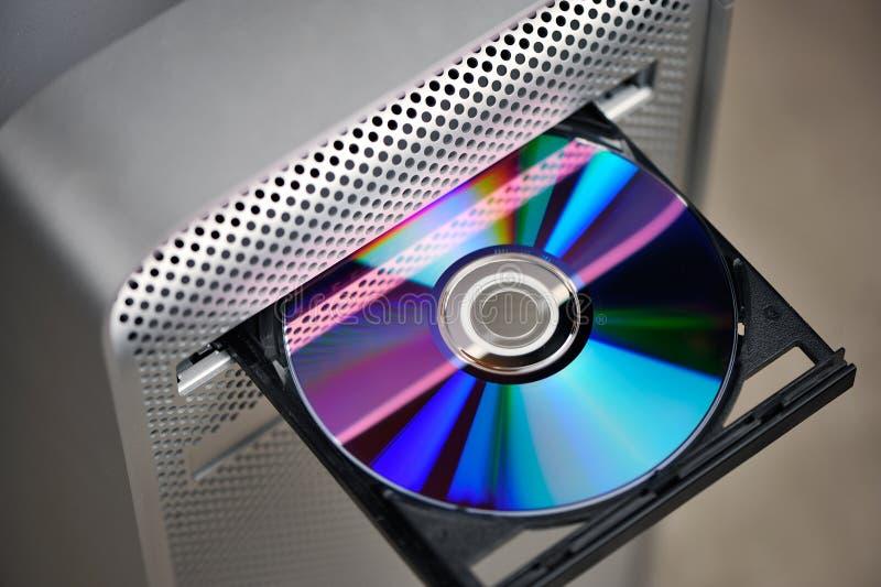 CD o DVD en mecanismo impulsor del ordenador fotos de archivo