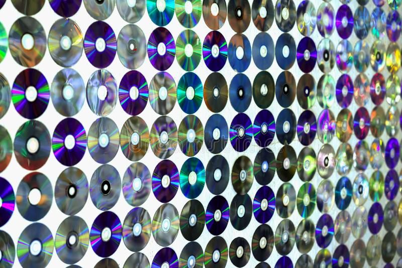 Cd viejo de los discos en la pared con con reflexiones coloridas multicoloras, fondo moderno imagenes de archivo