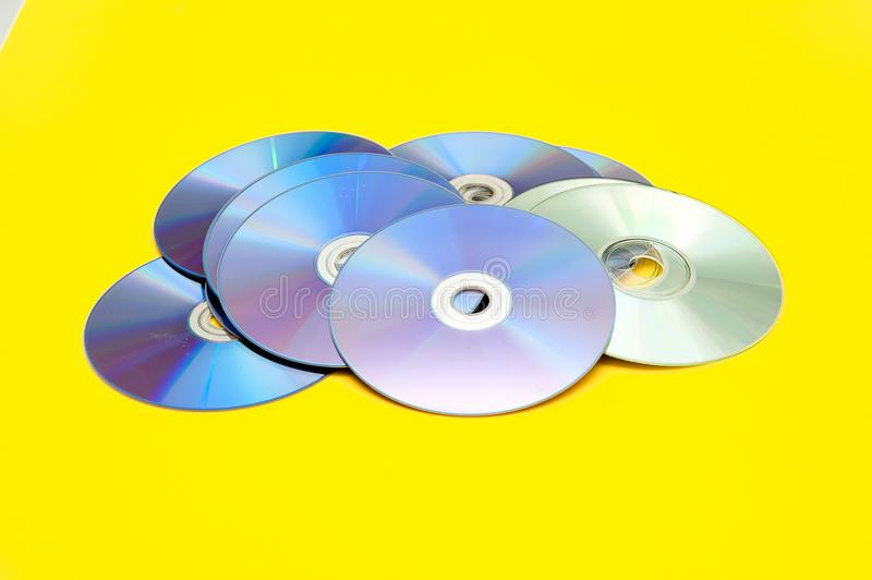 CDs, DVDs,. On a yellow background royalty free stock photography